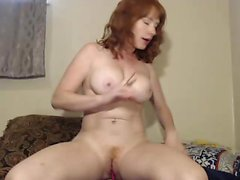 Redhead babe stripping and rubbing her boobs